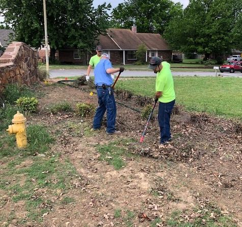 Volunteers cleaning out flowerbed at neighborhood entrance